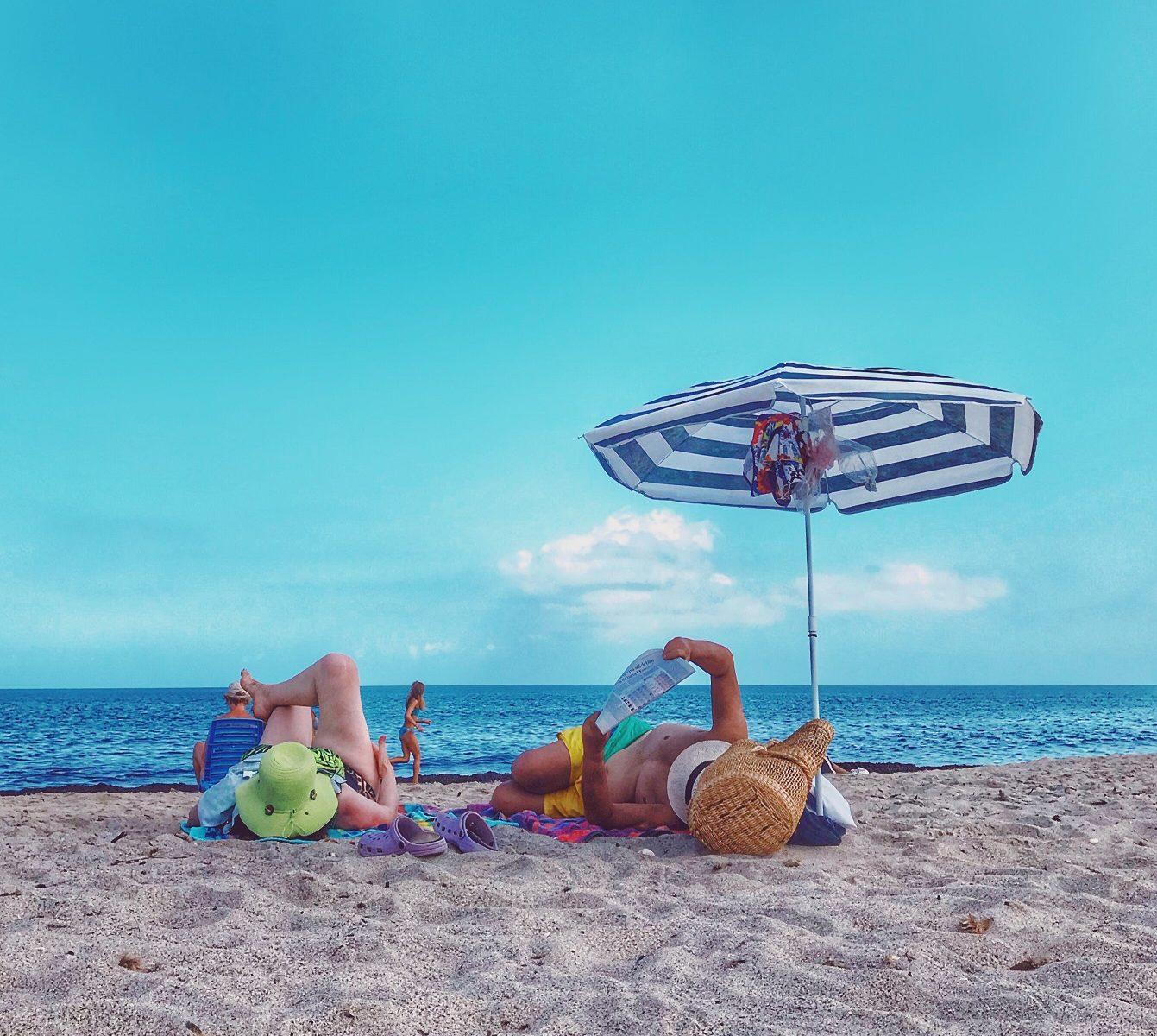 tourists on the beach under an umbrella