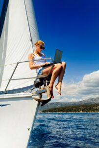 woman using laptop on bow of sailboat